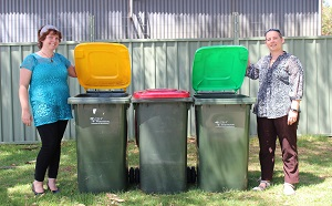 People standing next to three bins