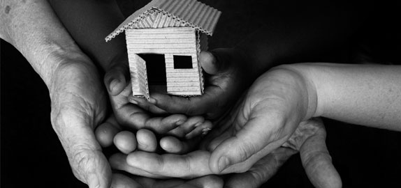 Photo of hands holding a house