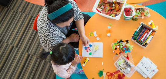 Child and parent doing activities at library