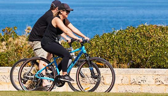 People riding bikes along coast